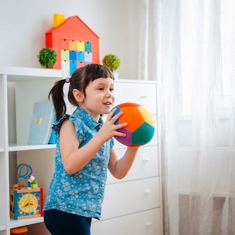 Kinder kleines mädchen spielen kinderspielzimmer, ball werfen. konzept interaktion eltern und kind