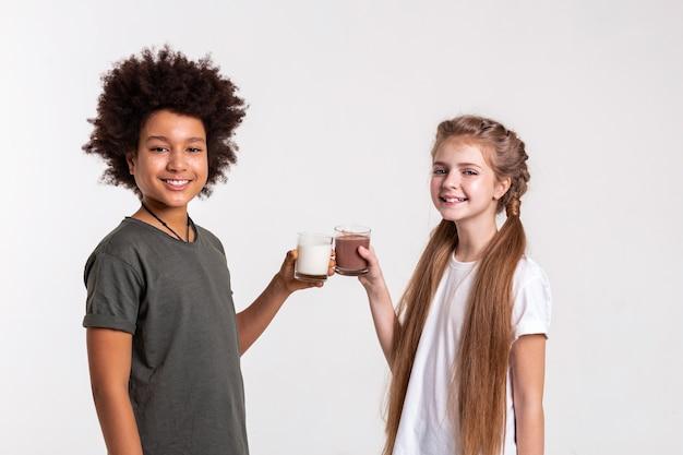 Kinder klirren mit brille. fröhliche, gut aussehende junge freunde, die milch und kakao halten und gläser berühren