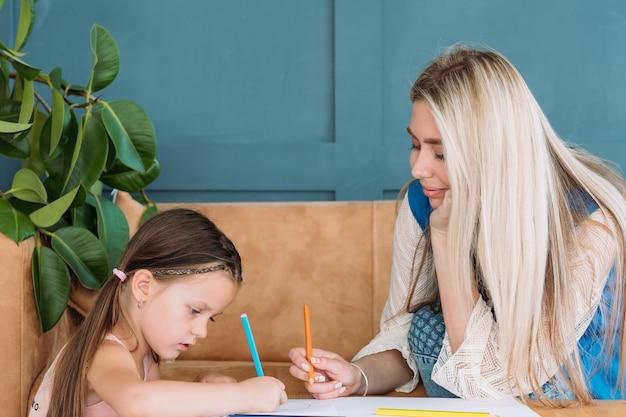 Kinder künstlerische freizeit. malerei kunst hobby. kleines mädchen und ihre mutter zeichnen bilder mit bleistiften.