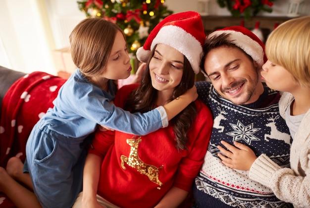Kinder küssen ihre eltern zu weihnachten