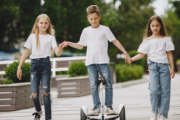 Kinder lernen an einem sonnigen sommertag in einem park hoverboard zu fahren