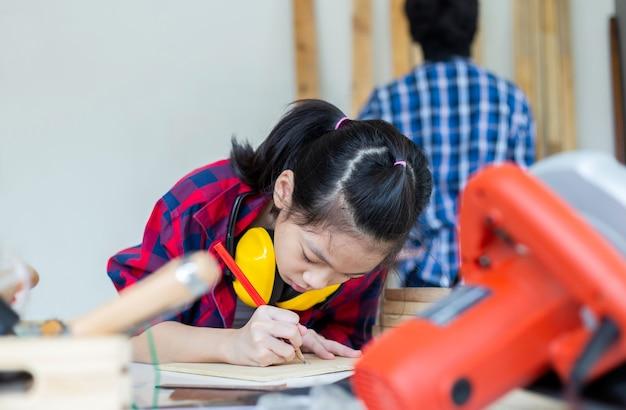 Kinder lernen holzbearbeitung in der handwerkerwerkstatt, teenager-junge mit seiner kleinen schwester, die zusammen in einer tischlerei eine werkstatt baut.