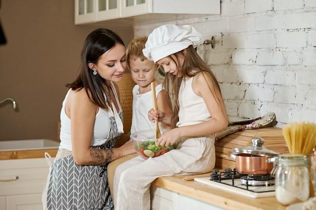 Kinder lernen in der küche, wie man einen salat zubereitet.