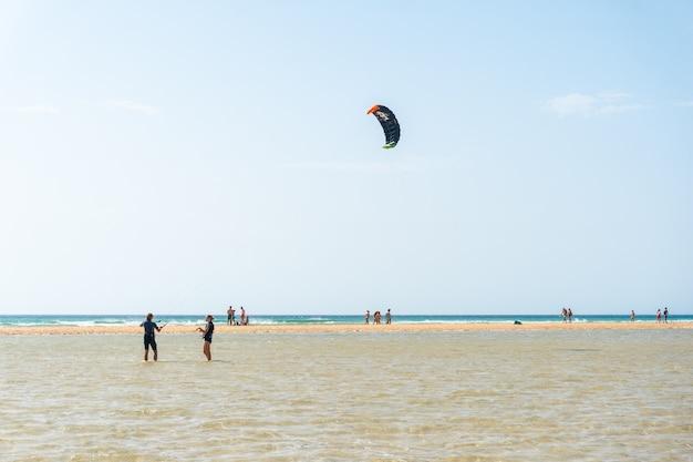 Kinder lernen kitesurfen oder skysurfen am strand von sotavento im süden von fuerteventura, kanarische inseln. spanien