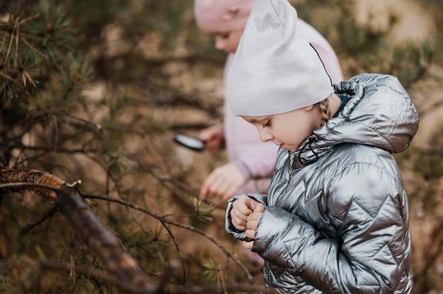 Kinder lernen wissenschaft in der natur mit einer lupe