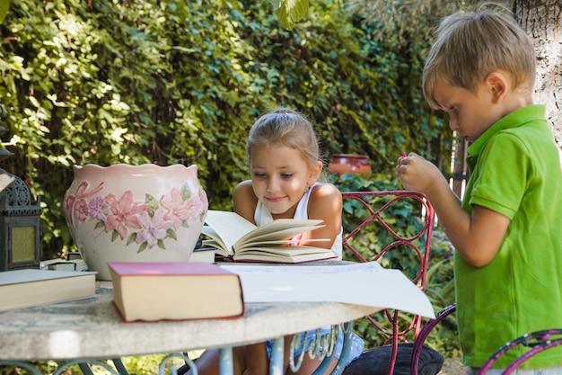 Kinder lesen am tisch im garten
