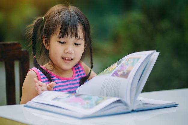 Kinder lesen ein buch und machen hausaufgaben.