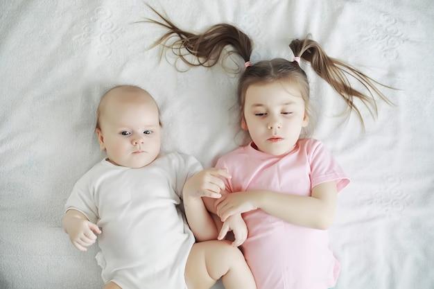Kinder liegen auf dem bett neben dem neugeborenen, kleine schwester. emotionen der kinder.