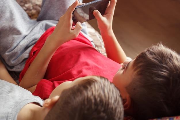 Kinder liegend ein handy zu spielen