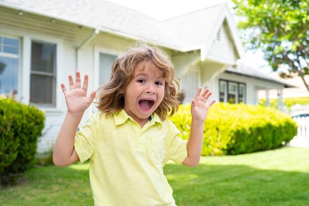 Kinder lustiges gesicht, das spaß im freien hat. glückliches kind, das draußen spaß auf hinterhof hat.