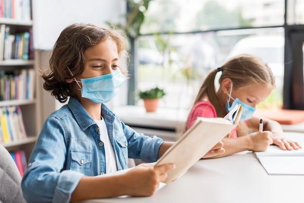 Kinder machen ihre hausaufgaben, während sie eine gesichtsmaske tragen