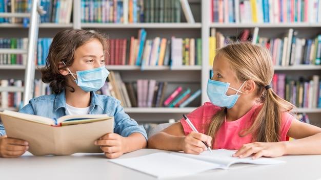 Kinder machen ihre hausaufgaben, während sie eine medizinische maske tragen