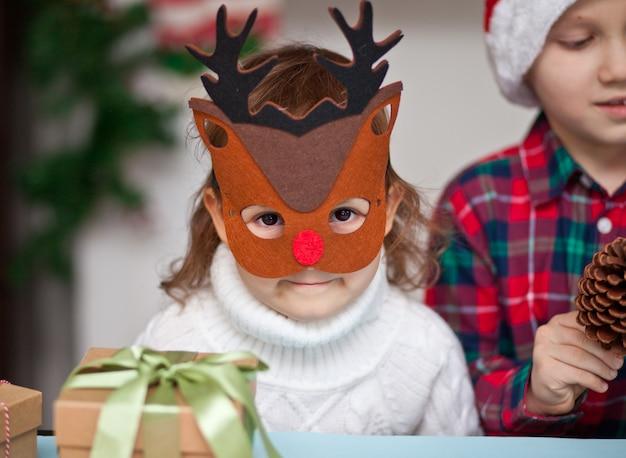 Kinder mädchen in hirschmaske und junge in santa mütze