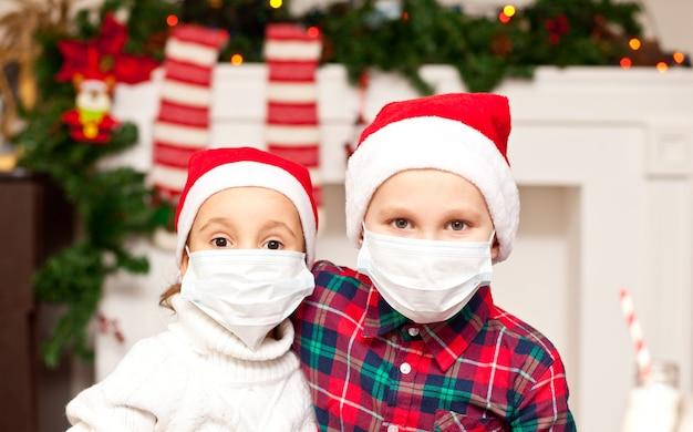 Kinder mädchen und junge in santa mützen in medizinischen masken gratulieren einander frohe weihnachten und ein gutes neues jahr und umarmen sich.