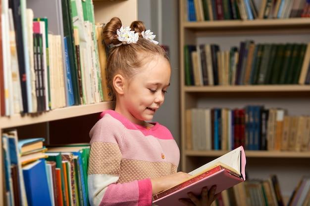Kinder mädchen werden mitgerissen, indem sie ein buch in der bibliothek lesen und zwischen mehrfarbigen bücherregalen stehen
