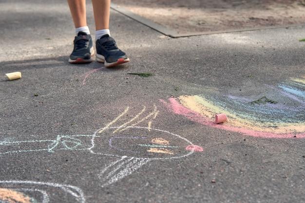 Kinder malen draußen. porträt eines kinderjungen, der an einem sonnigen sommertag eine regenbogenfarbene kreide auf den asphalt zeichnet. kinder spielen auf dem spielplatz. außenaktivität