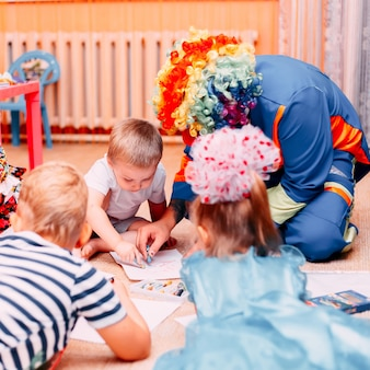 Kinder malen drow-papier auf dem boden mit clown