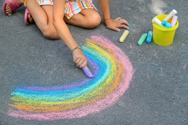 Kinder malen einen regenbogen auf den asphalt. selektiver fokus. kinder.
