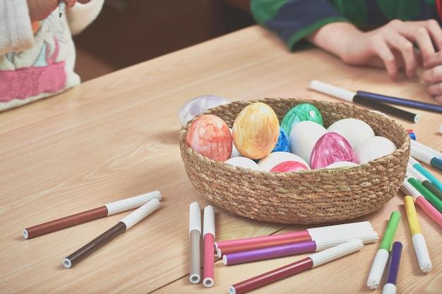 Kinder malen ostereier mit der hilfe ihrer mutter und mit markern zu hause