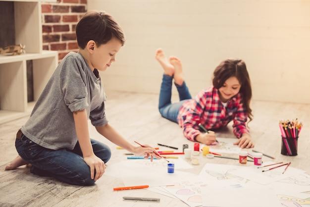 Kinder malen und lächeln, während sie auf dem boden liegen.