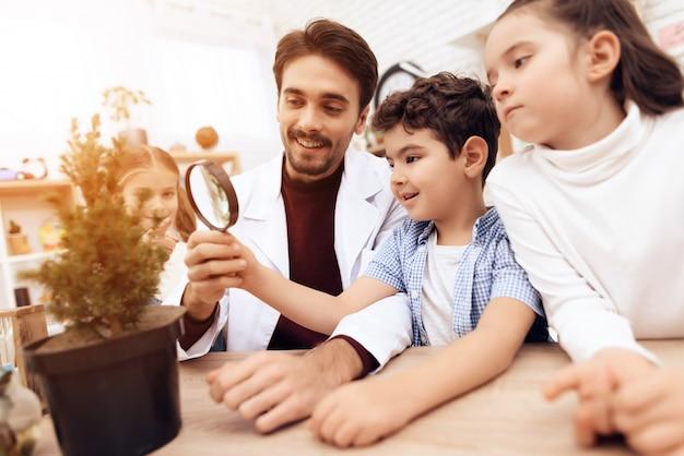 Kinder mit dem lehrer schauen durch eine lupe.