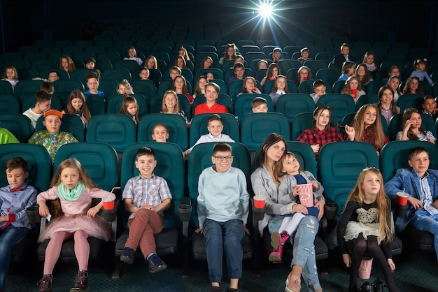 Kinder mit den eltern, die zusammen einen film im kino genießen