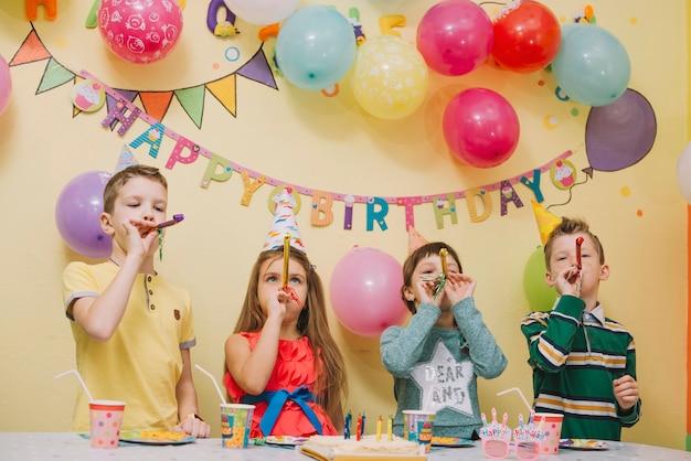Kinder mit den parteihörnern, die geburtstag feiern