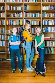 Kinder mit den schulrucksäcken, die in der bibliothek stehen