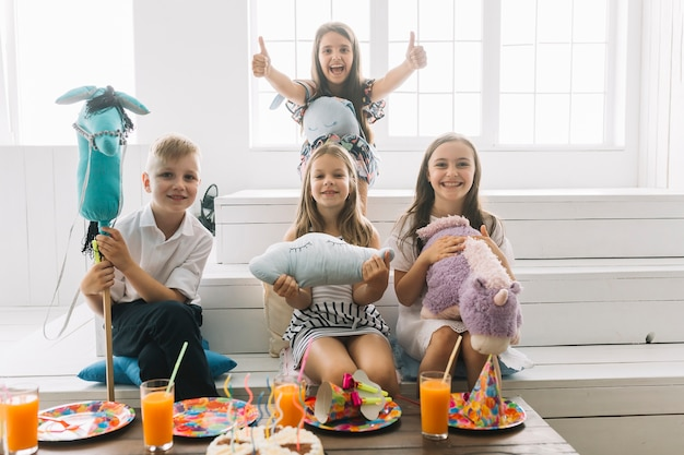 Kinder mit den spielwaren, die kamera während der geburtstagsfeier betrachten