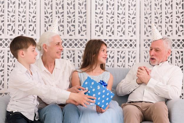 Kinder mit der großmutter, die ihrem glücklichen großvater das geschenk sitzt auf sofa gibt