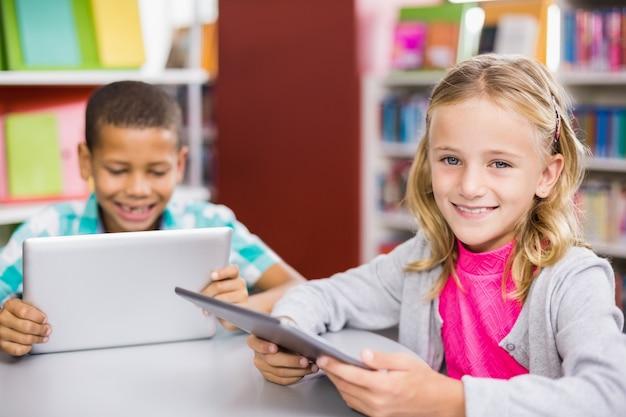 Kinder mit digitalem tablet in der bibliothek
