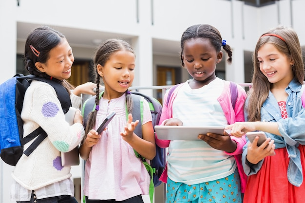 Kinder mit digitalem tablet und handy auf der schulterrasse