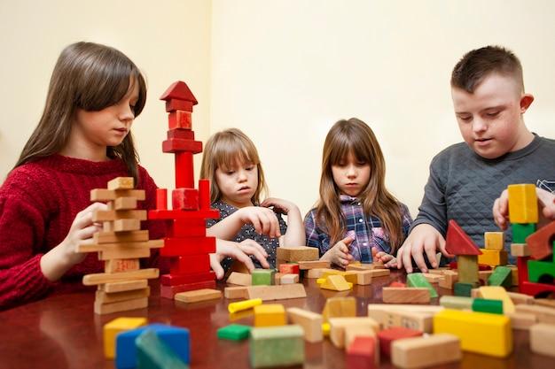 Kinder mit down-syndrom spielen mit blöcken