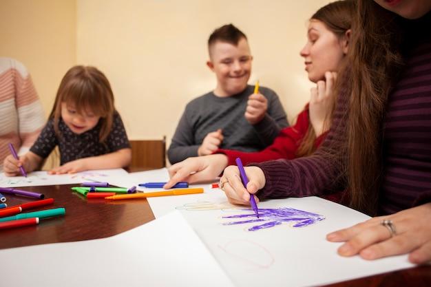 Kinder mit down-syndrom zeichnen und haben spaß