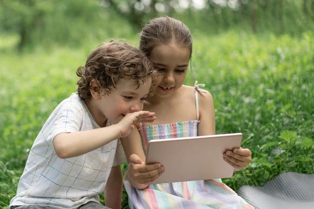 Kinder mit einem tablet im freien kinder sprechen per videoanruf-technologiekonzept