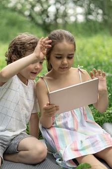 Kinder mit einem tablet im freien kinder sprechen per videoanruf