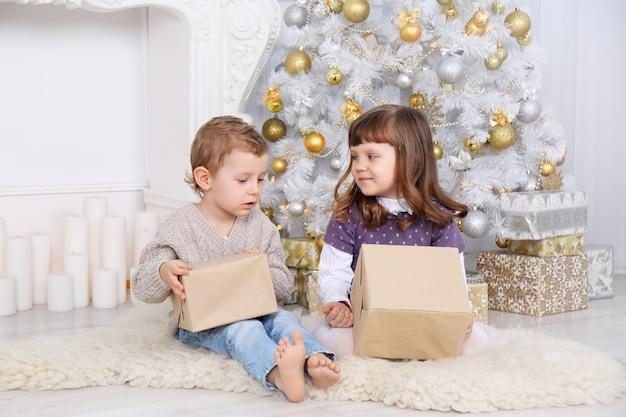 Kinder mit geschenken unter dem weihnachtsbaum
