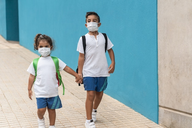 Kinder mit gesichtsmaske, die während des ausbruchs des coronavirus zur schule zurückkehren - fokus auf jungengesicht