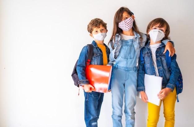 Kinder mit gesichtsmasken, die ihre schulsachen halten und an einer wand stehen - covid-19