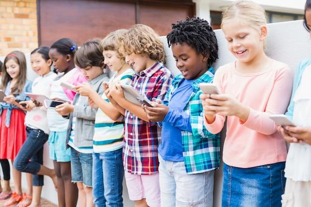 Kinder mit handy und digitalem tablet auf der schulterrasse