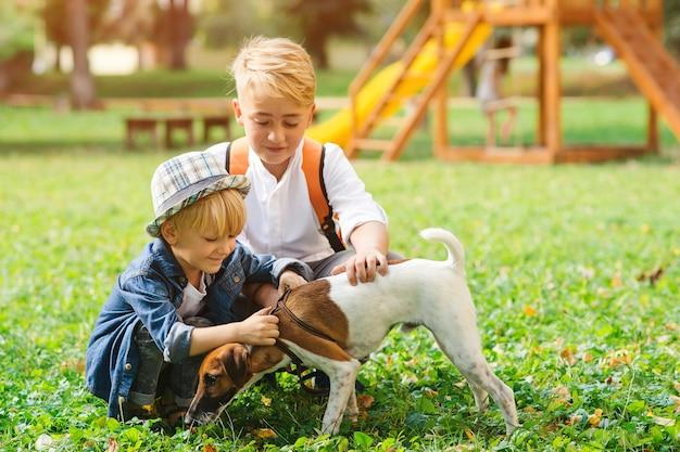 Kinder mit hund im park spazieren. familie, freundschaft, tiere und lebensstil. kinder mit jack russell terrier hund im freien.