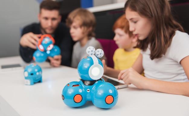 Kinder mit lehrer, die roboter schaffen