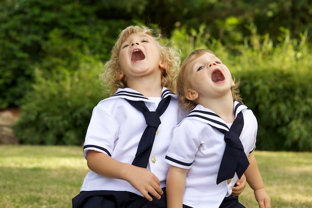 Kinder mit offenem mund auf einem feld, umgeben von viel grün im sonnenlicht
