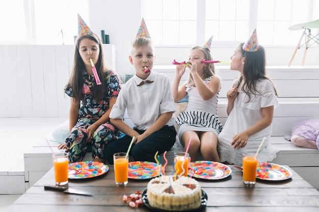 Kinder mit partygebläsen nahe geburtstagskuchen und -getränken