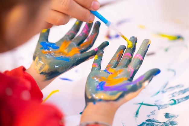 Kinder mit schmutziger gemalter hand im kunstklassenzimmer