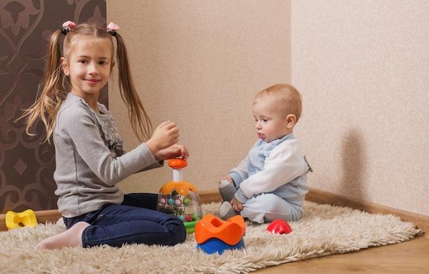 Kinder mit spielzeug auf dem boden