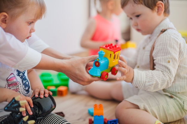 Kinder mit spielzeug und krankenschwester im spielzimmer