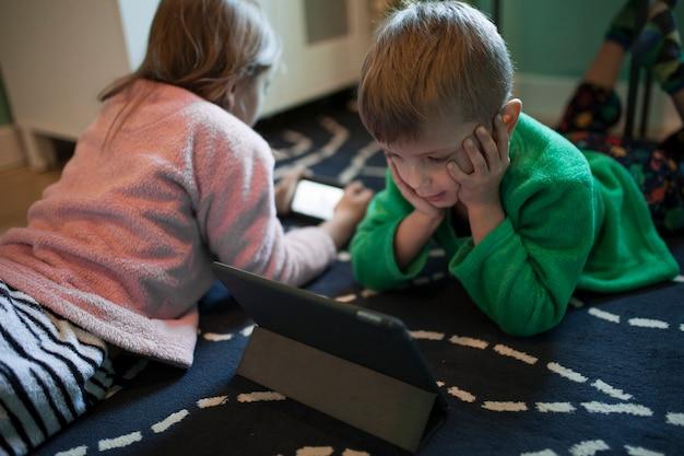 Kinder mit technologien auf dem boden