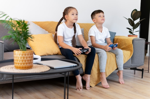 Kinder mit vollem schuss, die mit controllern spielen