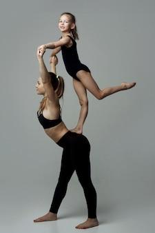 Kinder mit weiblichem lehrer, der mädchen ausbildet, gymnastik praktiziert, in bewegung steht. akrobatik im weißen loftstudio-hintergrund